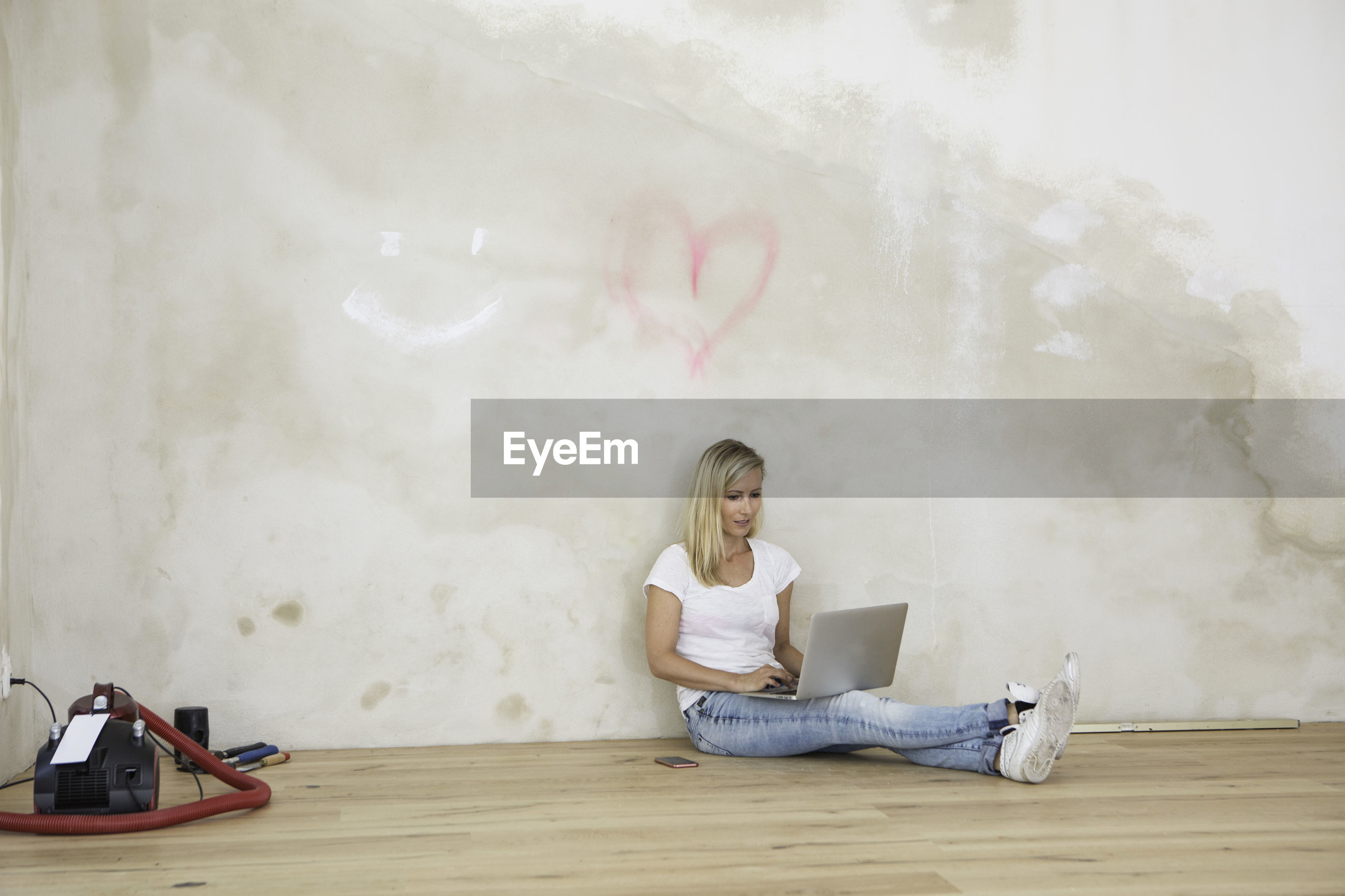 Close-up of young woman sitting on floor using laptop in empty room