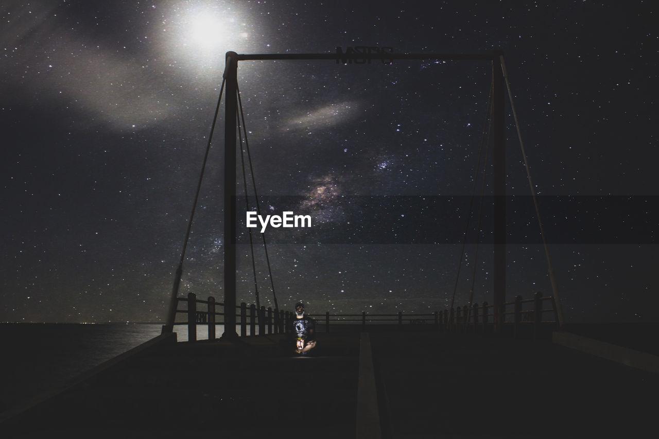 Silhouette man sitting on bridge against sky at night