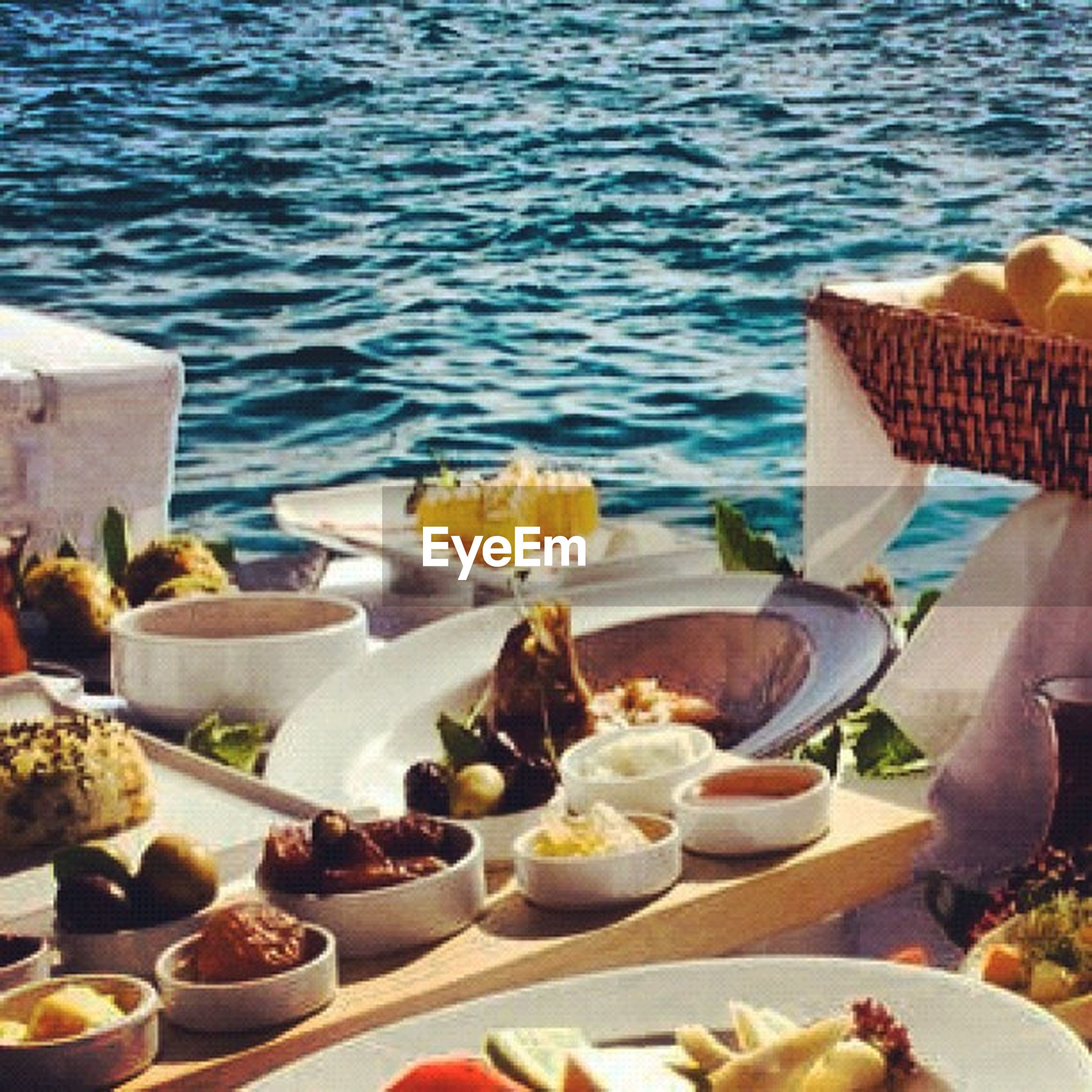 water, sea, table, food and drink, plate, chair, beach, freshness, high angle view, restaurant, day, sunlight, place setting, relaxation, food, arrangement, lounge chair, variation, tablecloth, summer