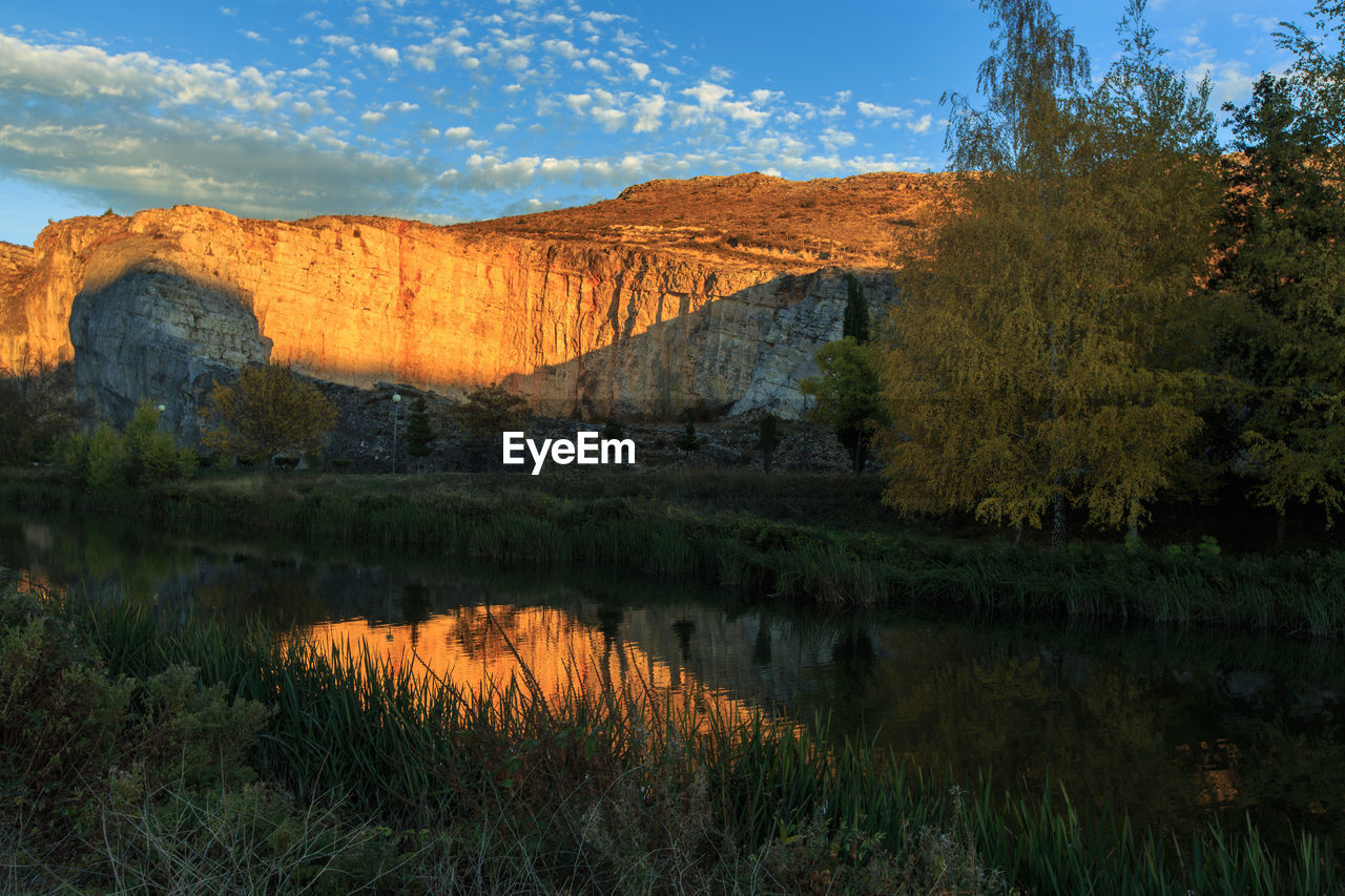 SCENIC VIEW OF LAKE BY ROCK FORMATION AGAINST SKY