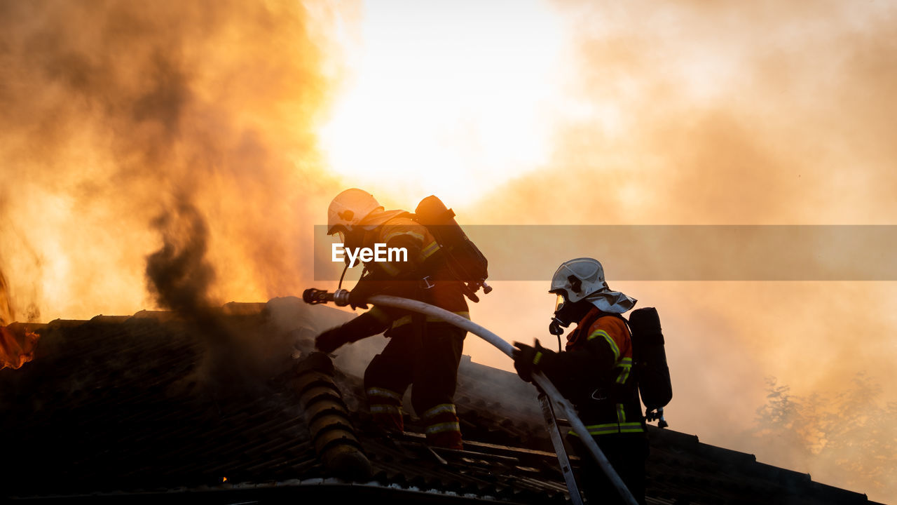 Low Angle View Of Firefighters With Fire Hose Against Smoke
