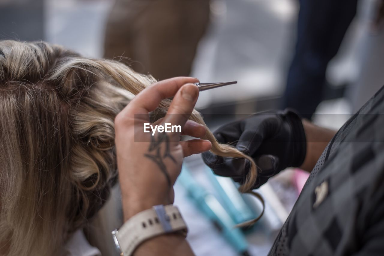 Cropped hands of hairdresser by woman in salon