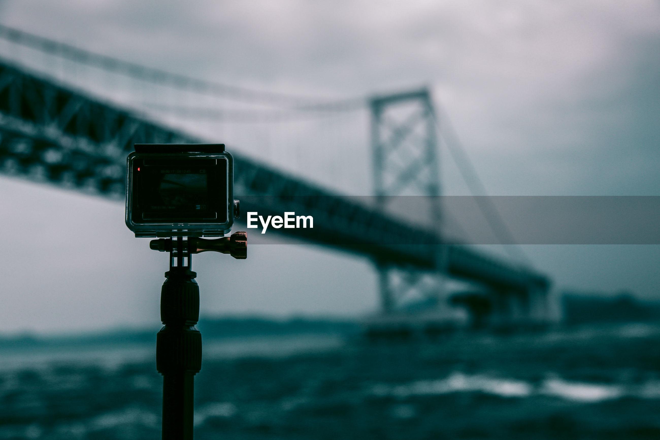 Close-up of tripod camera with onaruto bridge over sea in background