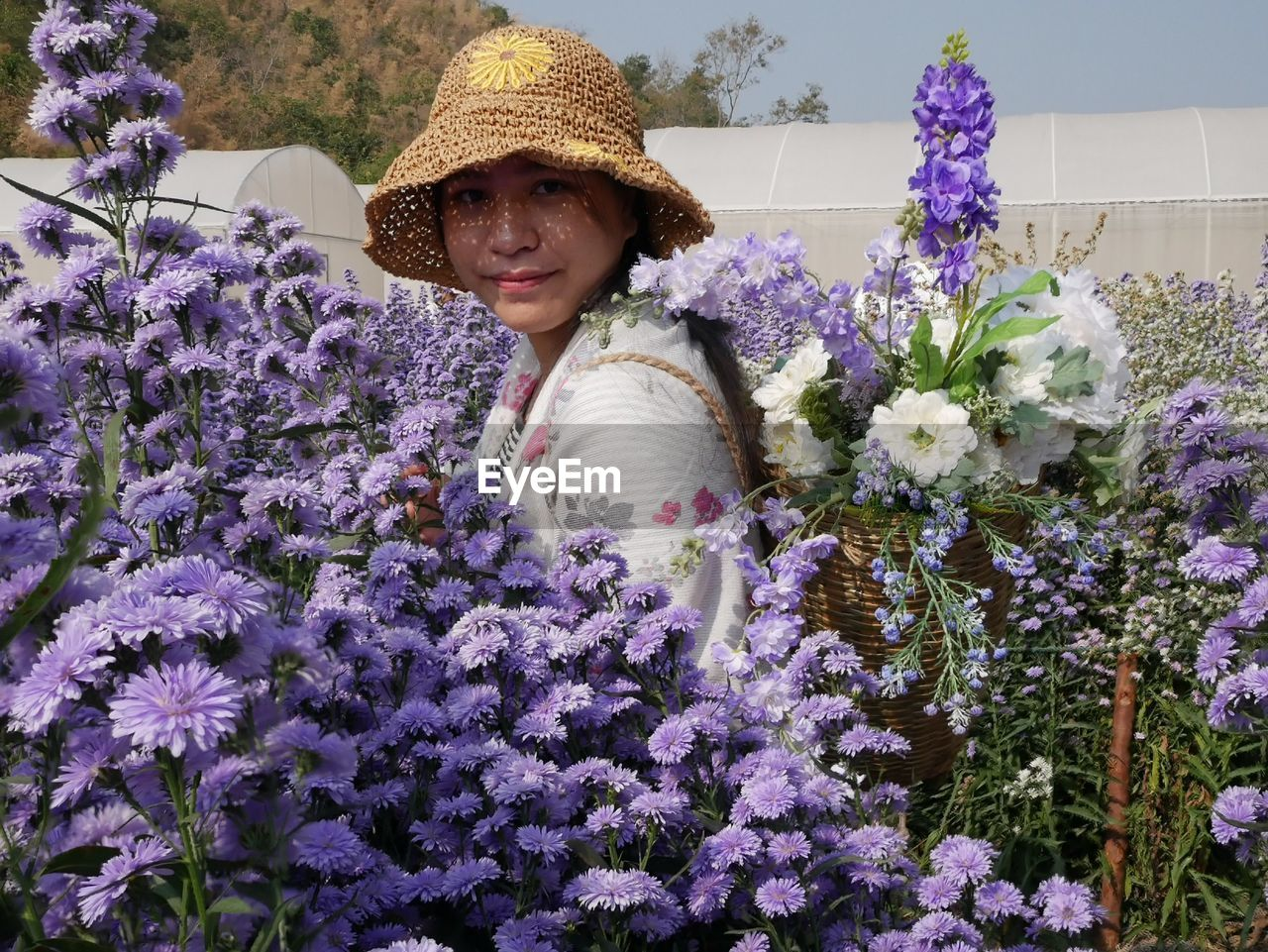 PORTRAIT OF SMILING WOMAN WITH PURPLE FLOWERS IN GARDEN