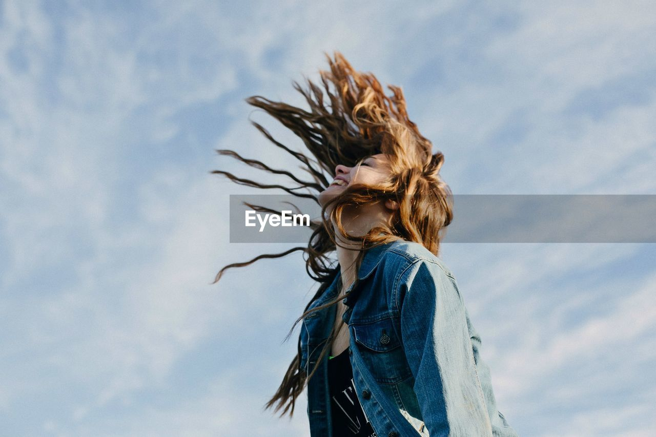 Low Angle View Of Smiling Woman Tossing Hair Against Sky
