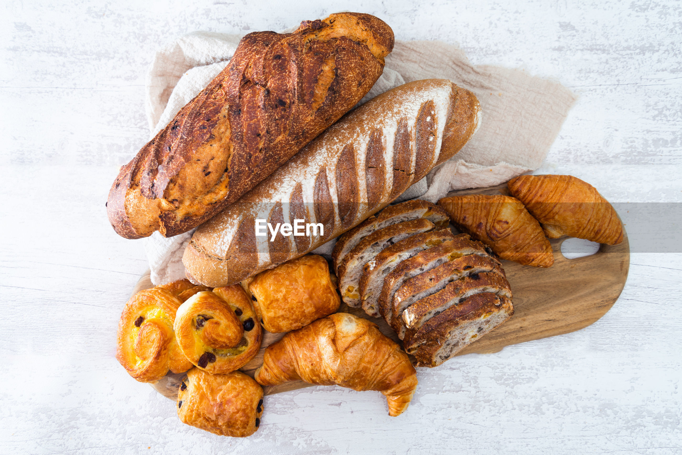 Directly above shot of breads and croissants on cutting board over table