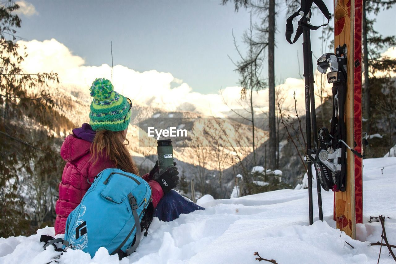snow, winter, cold temperature, warm clothing, real people, weather, field, knit hat, two people, leisure activity, rear view, lifestyles, day, nature, tree, togetherness, outdoors, ski holiday, sky