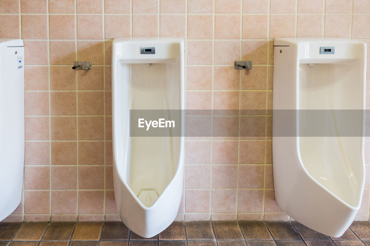 bathroom, tile, flooring, toilet, indoors, tiled floor, domestic bathroom, urinal, hygiene, public restroom, no people, wall - building feature, home, domestic room, convenience, public building, white color, absence, urgency, clean