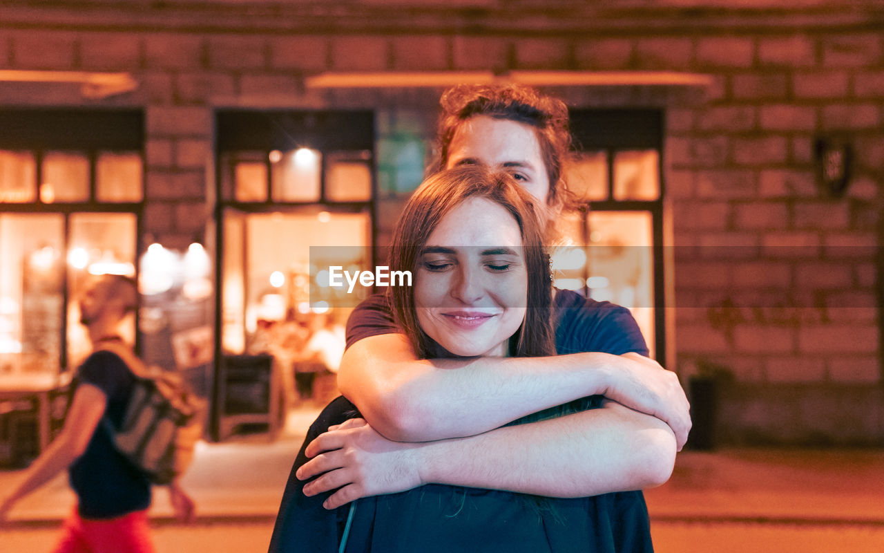 Portrait Of Smiling Young Man Embracing Woman On Street At Night