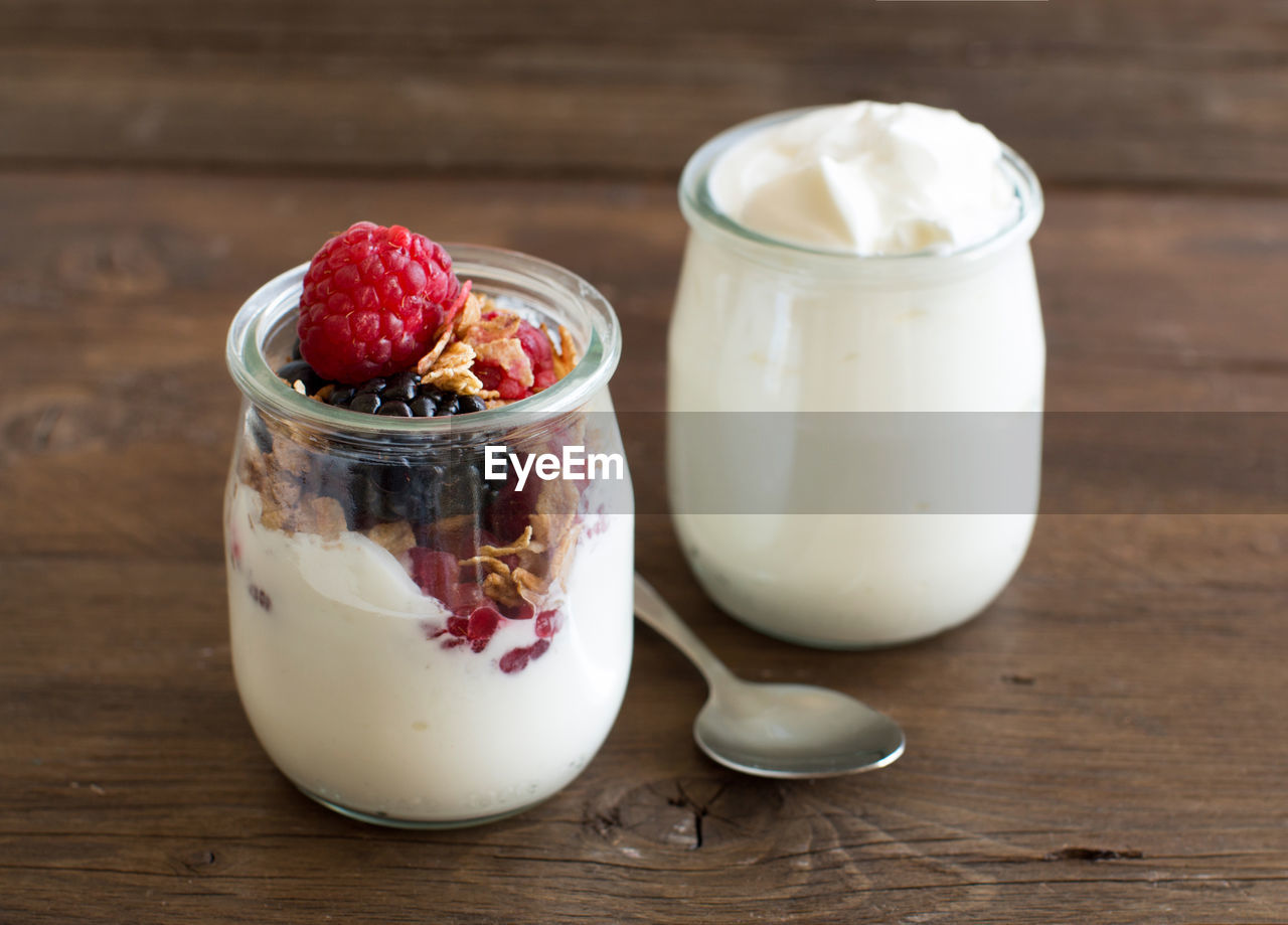 food and drink, table, food, healthy eating, wellbeing, freshness, still life, fruit, berry fruit, wood - material, indoors, container, no people, close-up, jar, yogurt, strawberry, raspberry, dairy product, focus on foreground, temptation, breakfast