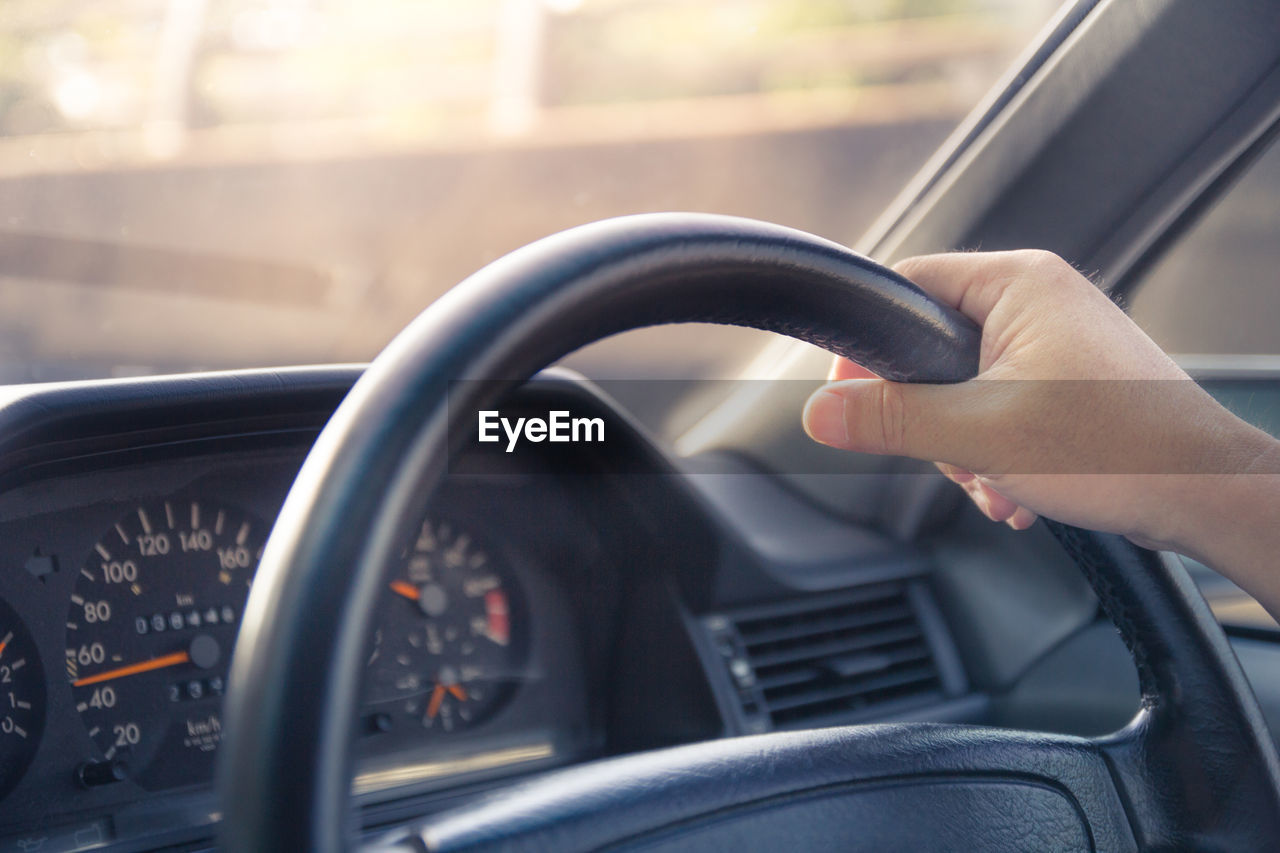 CROPPED IMAGE OF HAND ON CAR
