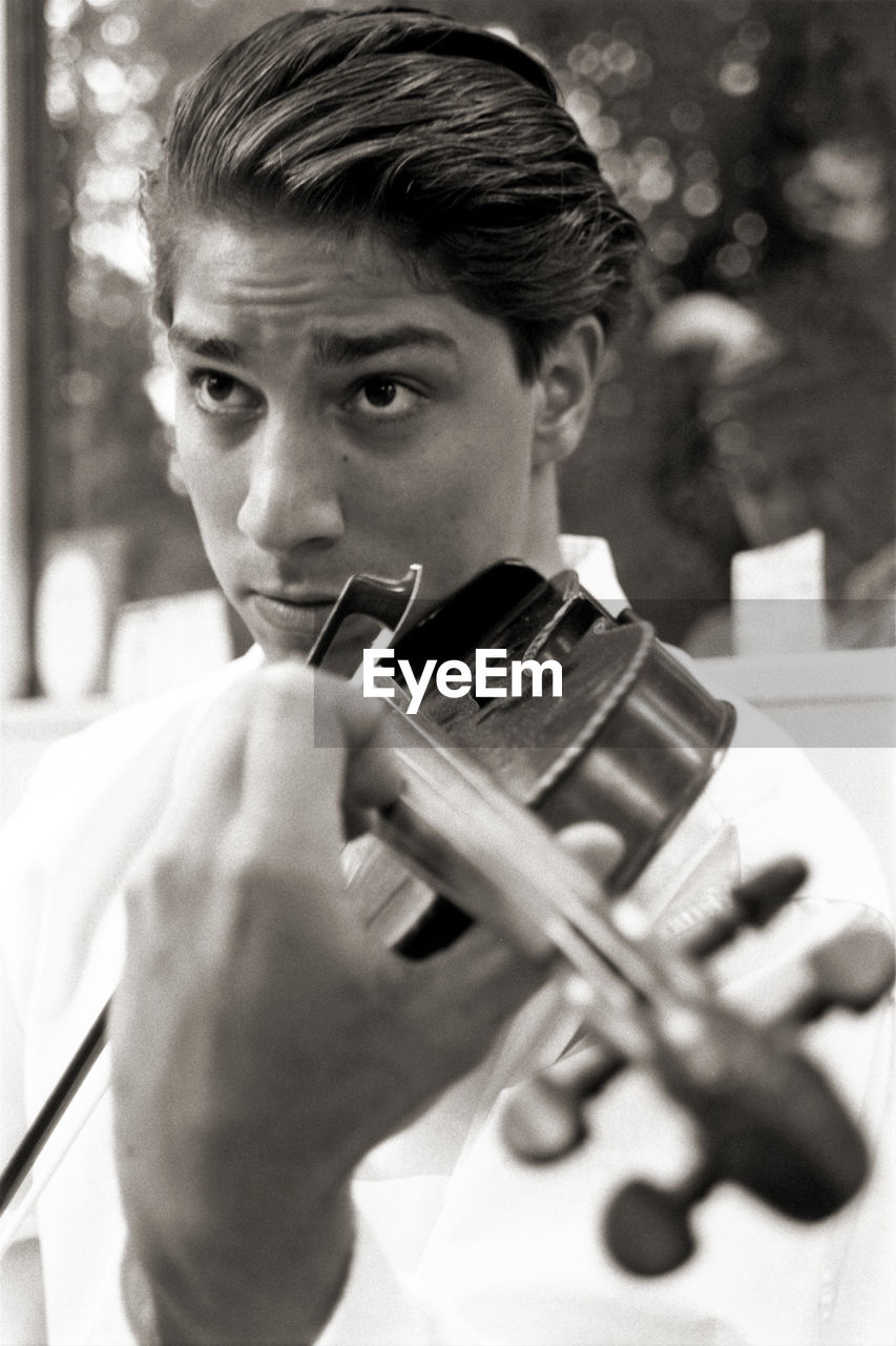 Close-up of man playing violin while standing outdoors