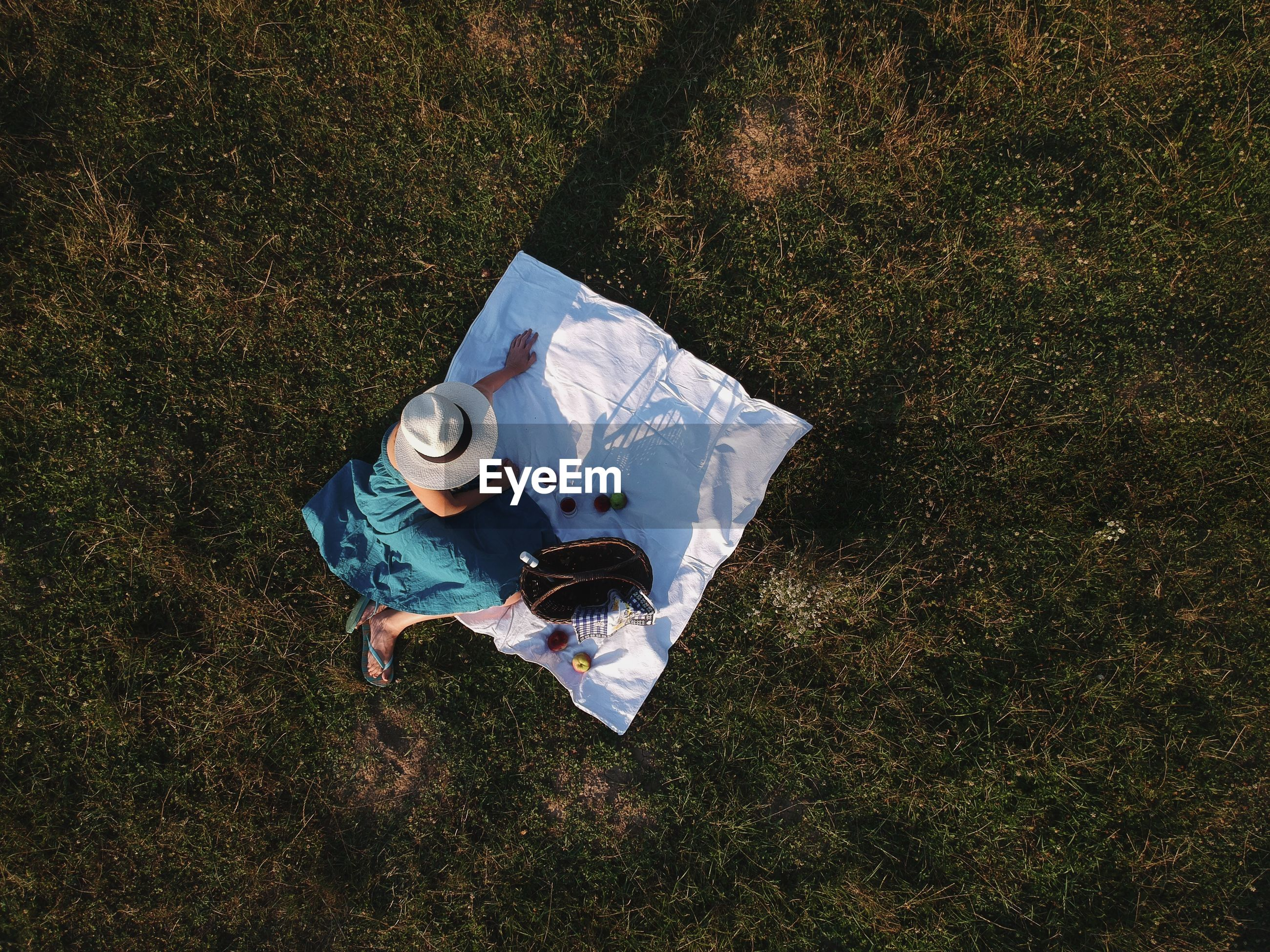 High angle view of woman sitting on picnic blanket on field