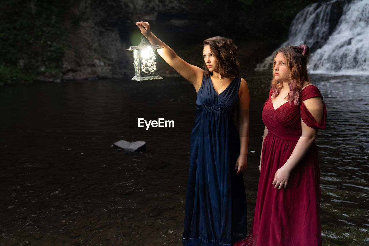 Girl holding lantern while standing at cave with friend