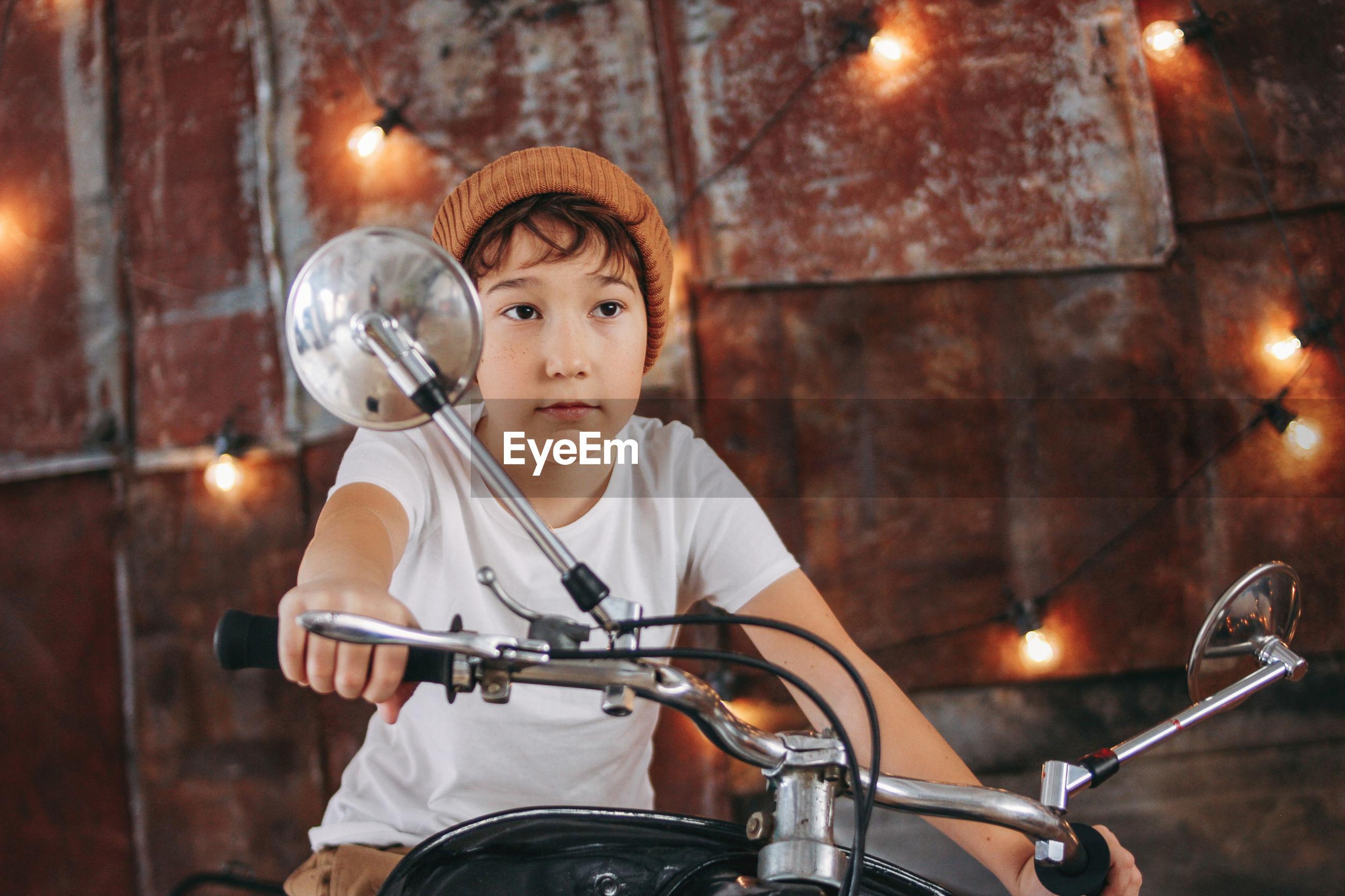 FULL LENGTH OF BOY HOLDING BICYCLE AT ILLUMINATED SHOP