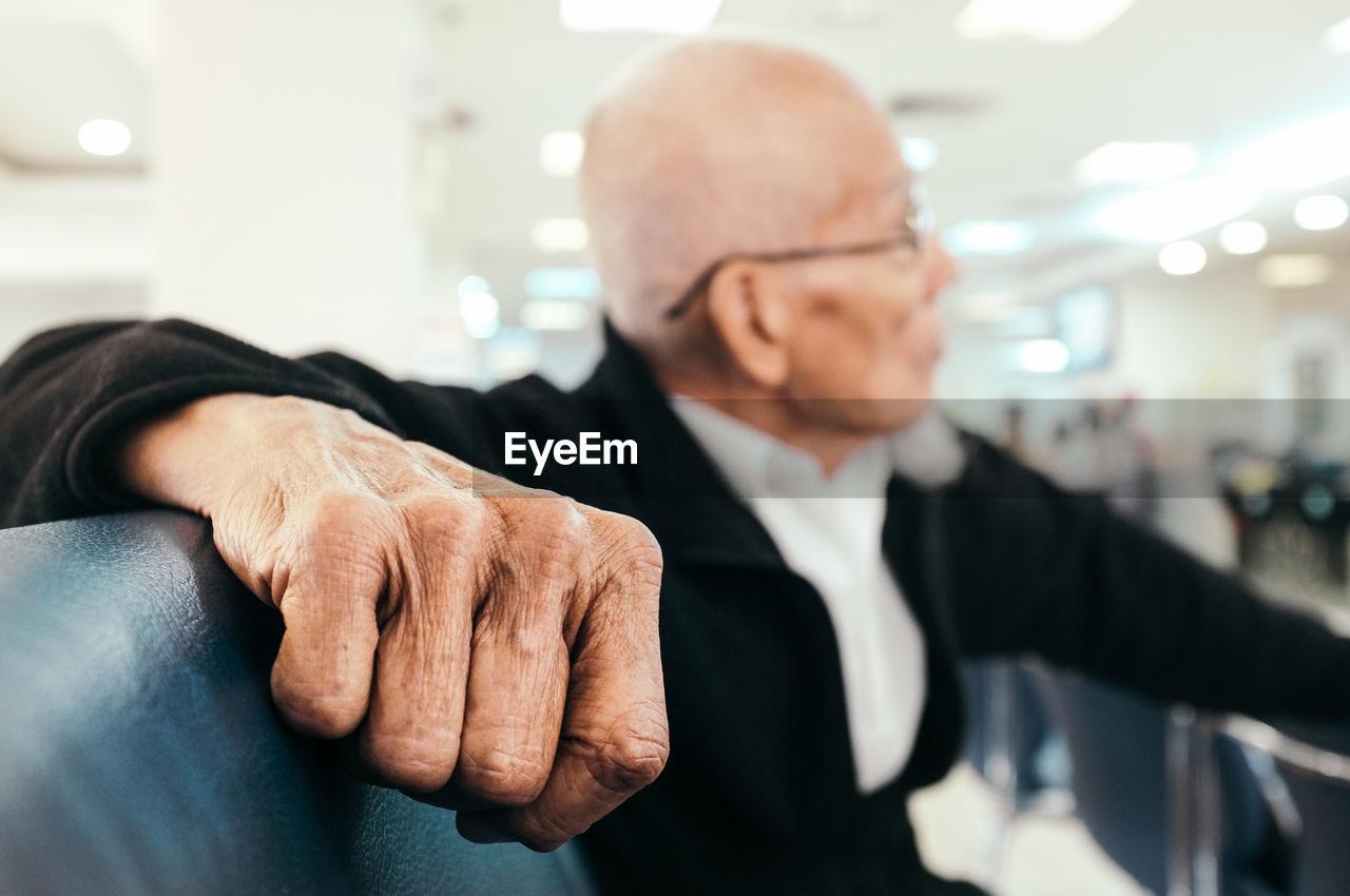 Close-Up Of Senior Businessman Sitting On Seat