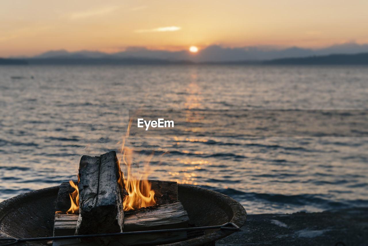 Wood Burning Against Sea During Sunset