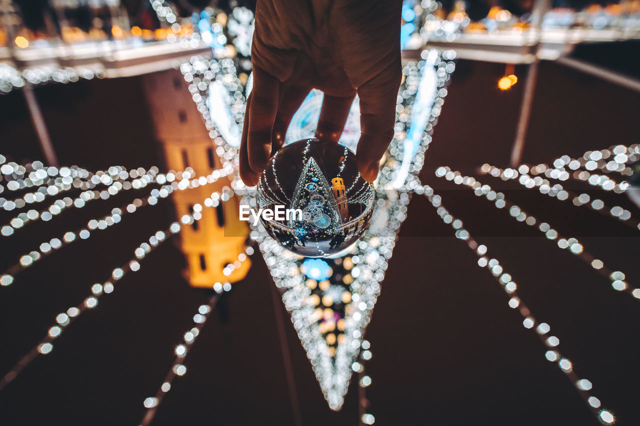 Cropped Hand Holding Crystal Ball Against Illuminated Lighting Equipment At Night