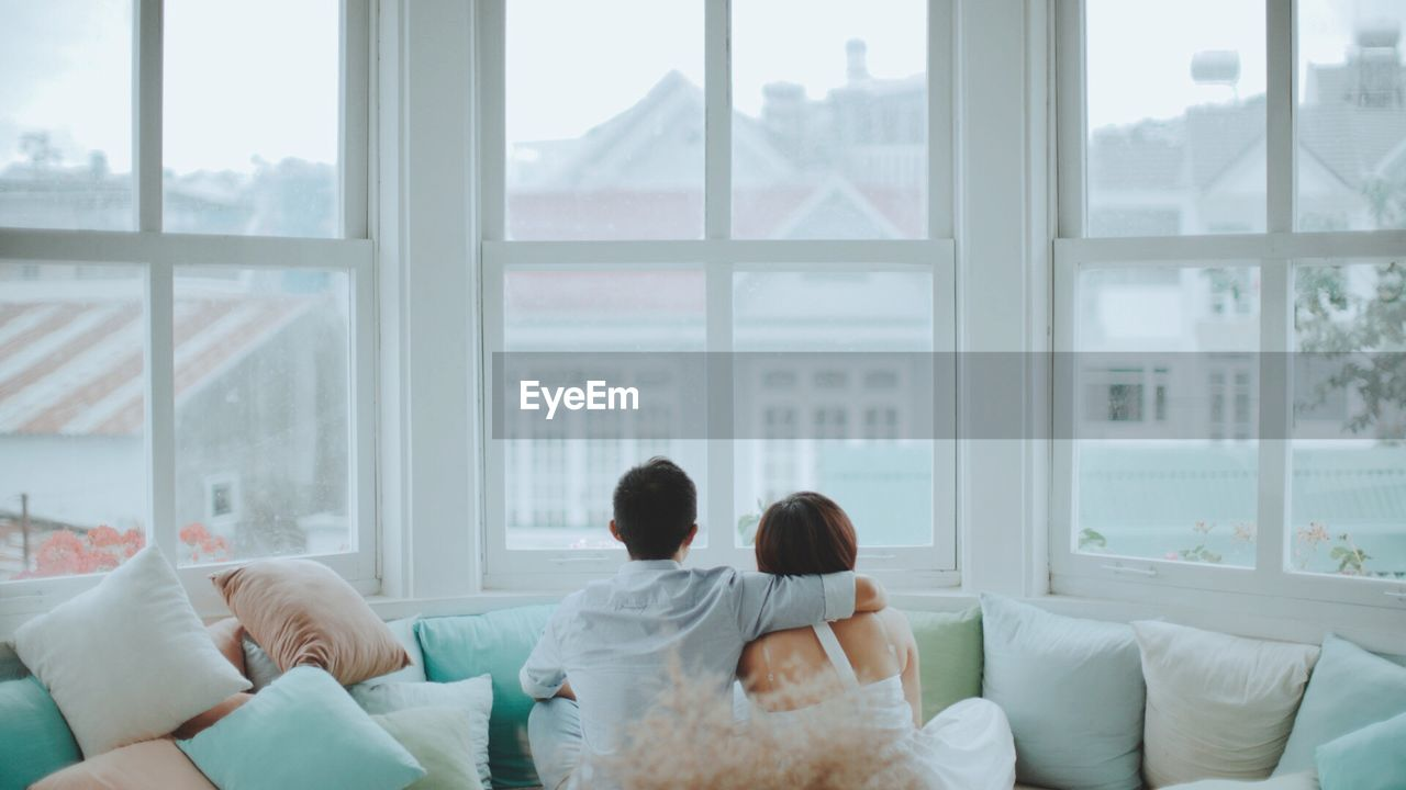 Rear View Of Couple Looking Through Bay Window