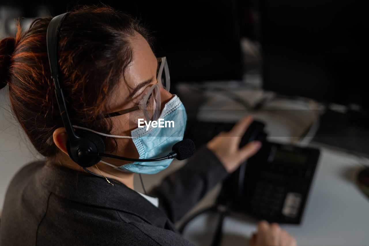 Rear view of woman using mask looking away at office