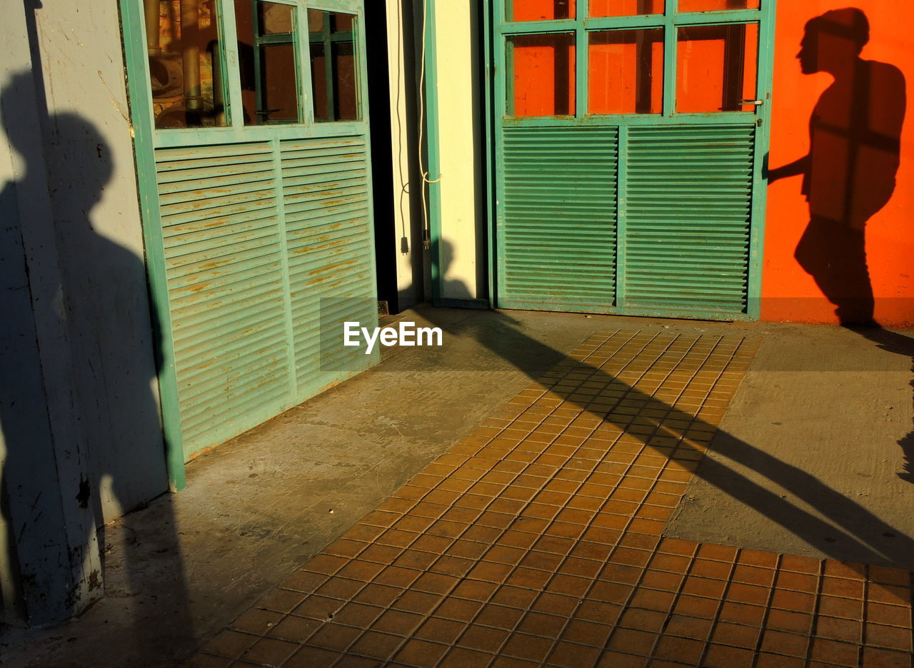 Shadow of person on footpath and door