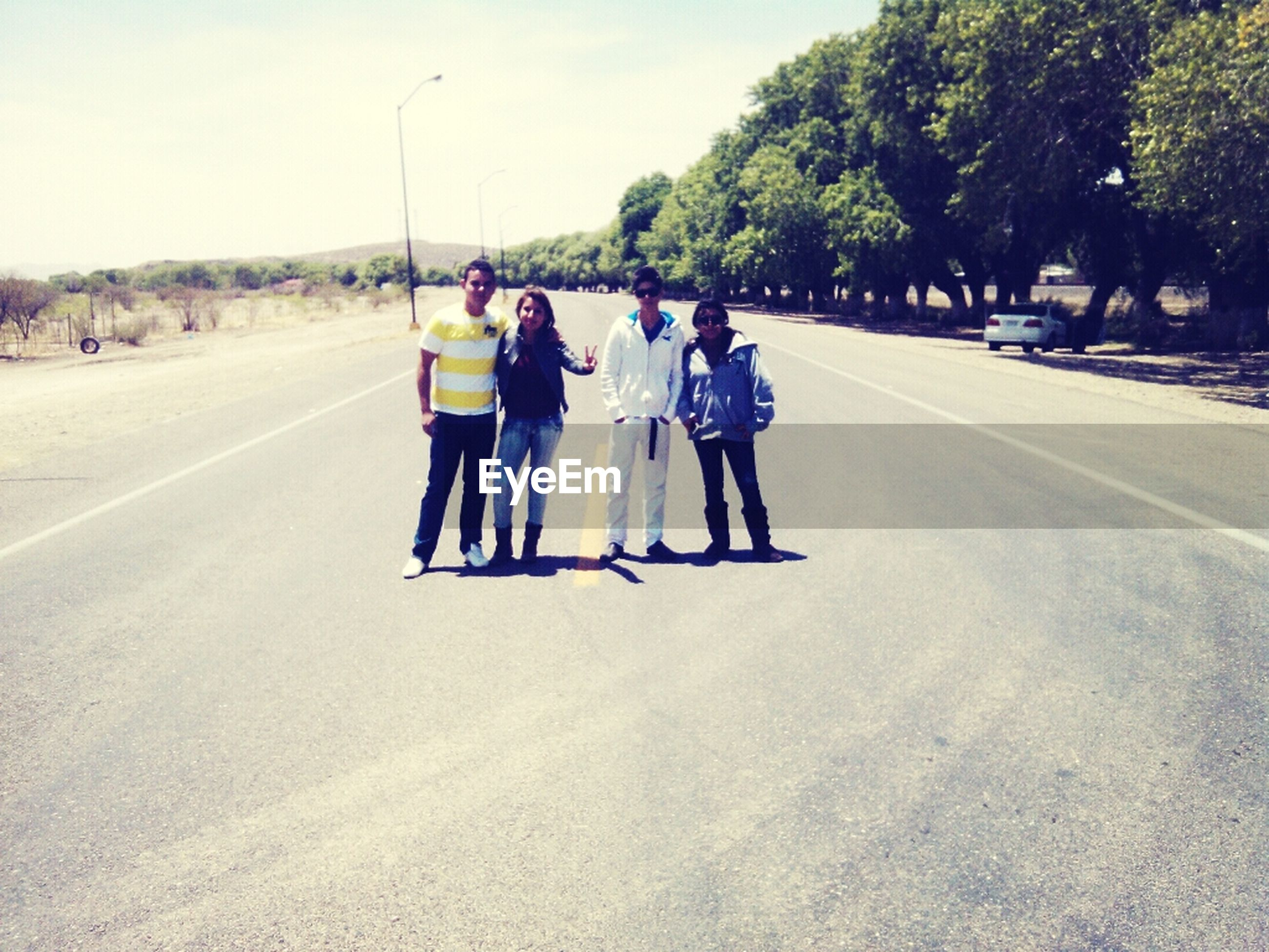 full length, lifestyles, togetherness, leisure activity, road, the way forward, tree, transportation, rear view, walking, men, casual clothing, sky, bonding, boys, day, friendship
