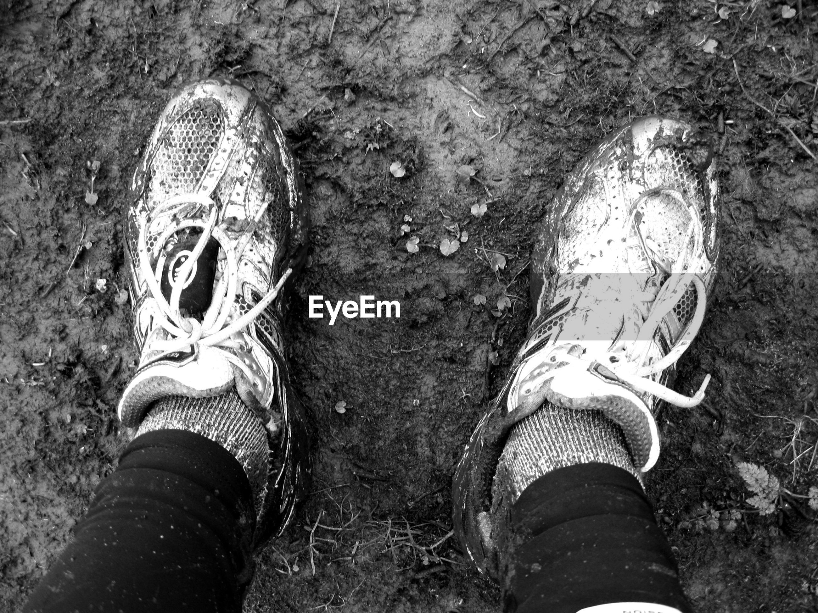 Low section of person with dirty shoes