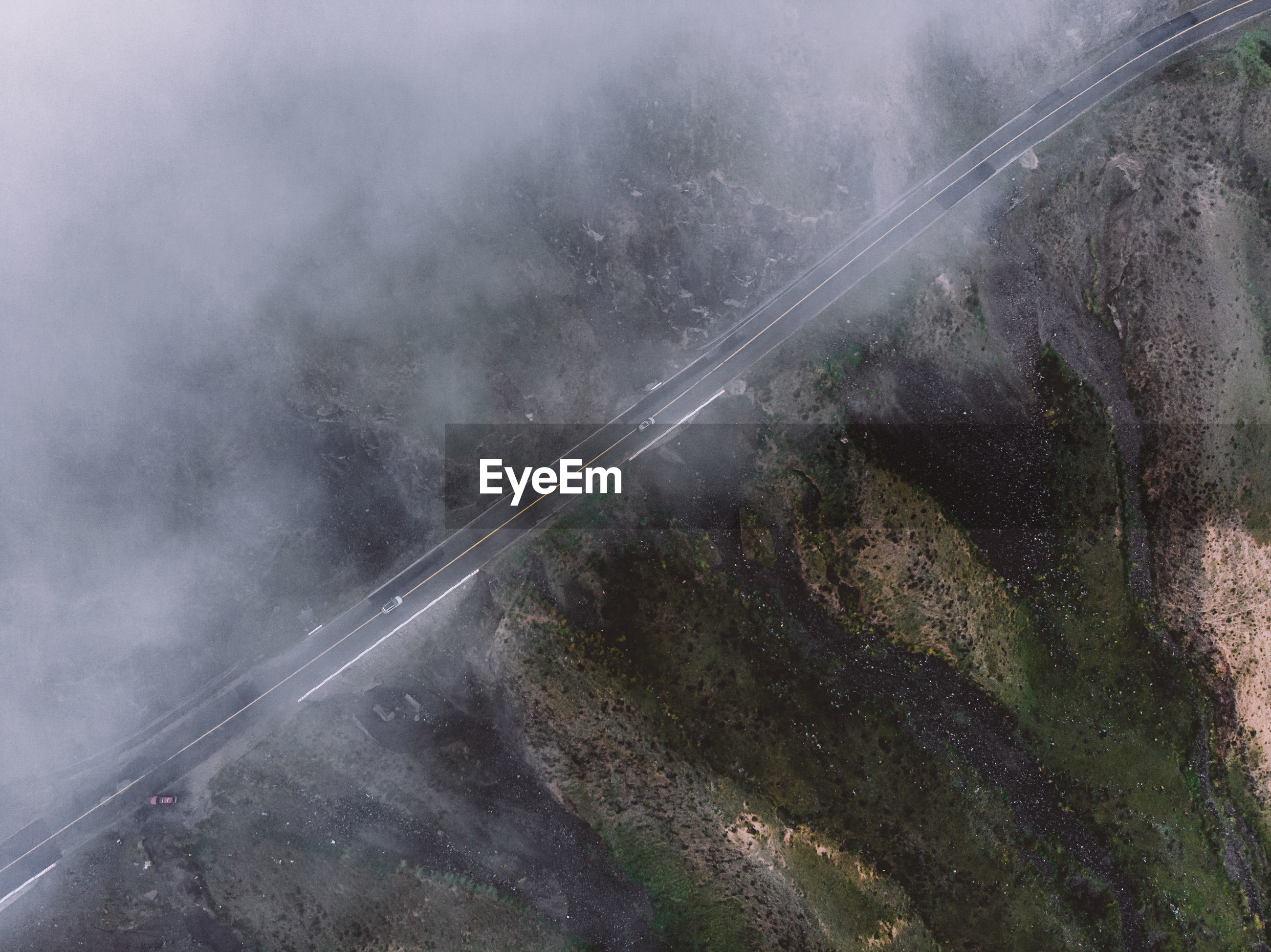 HIGH ANGLE VIEW OF ROAD AMIDST TREES AND MOUNTAINS