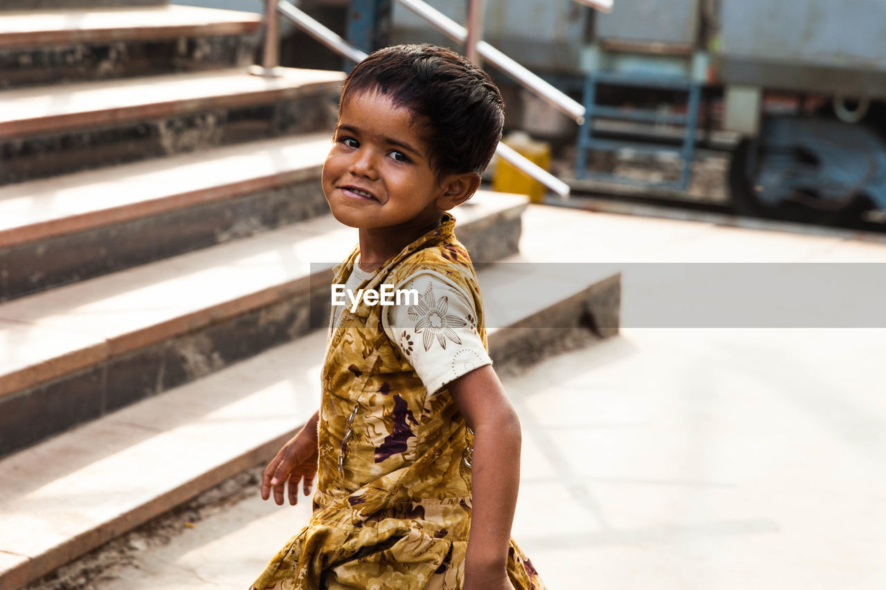 real people, childhood, one person, child, portrait, looking at camera, lifestyles, focus on foreground, casual clothing, smiling, leisure activity, standing, staircase, three quarter length, females, women, innocence, outdoors, hairstyle