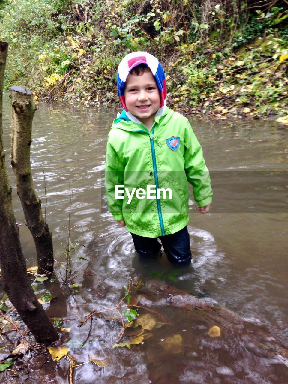 real people, boys, childhood, one person, looking at camera, elementary age, portrait, water, front view, smiling, outdoors, day, happiness, one boy only, full length, tree, adventure, standing, lifestyles, nature, people