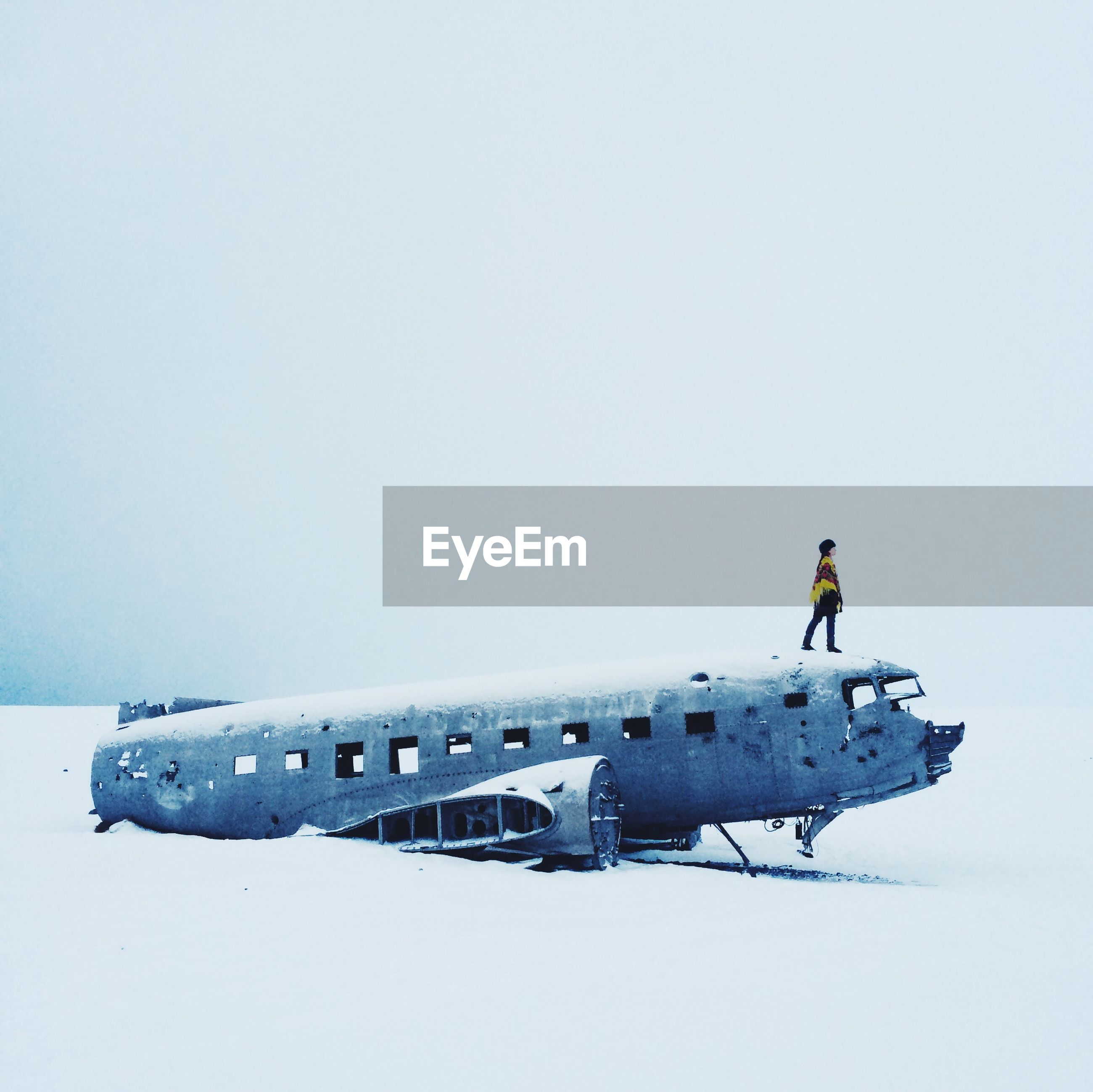 Full length of woman standing on abandoned airplane against sky during winter