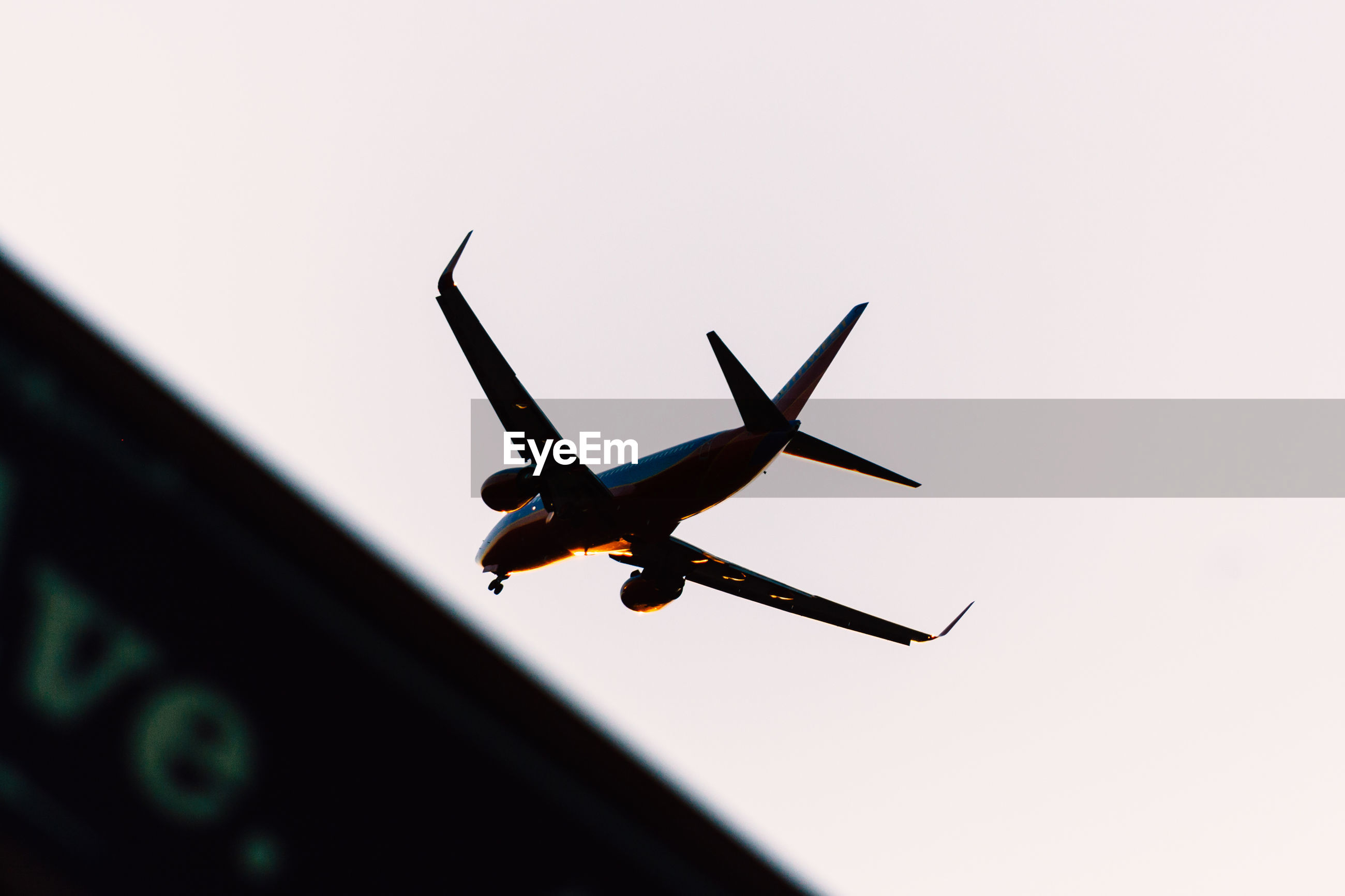 Low angle view of silhouette airplane flying against clear sky during sunset