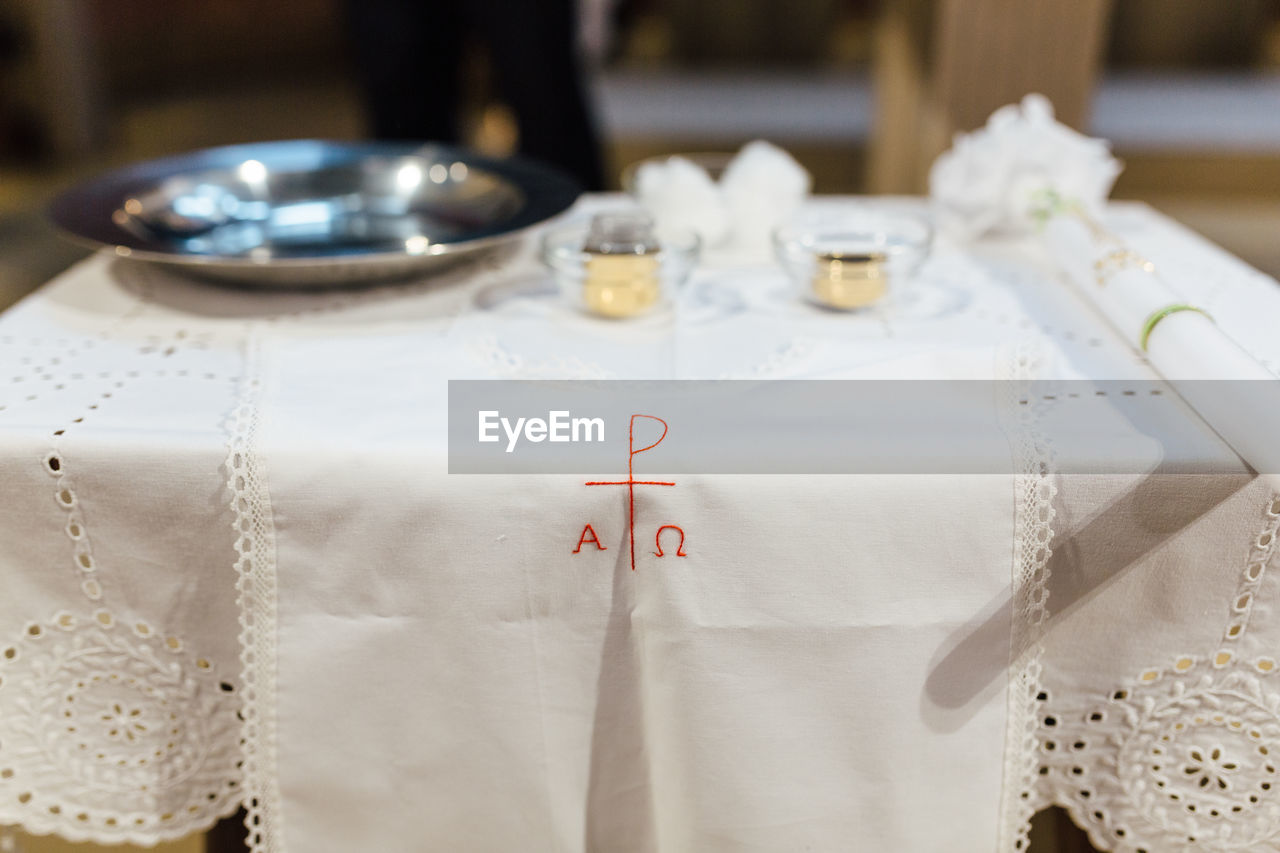 indoors, no people, table, white color, still life, text, close-up, communication, focus on foreground, textile, number, tablecloth, napkin, household equipment, wedding, event, day, paper, hanging, plate, setting