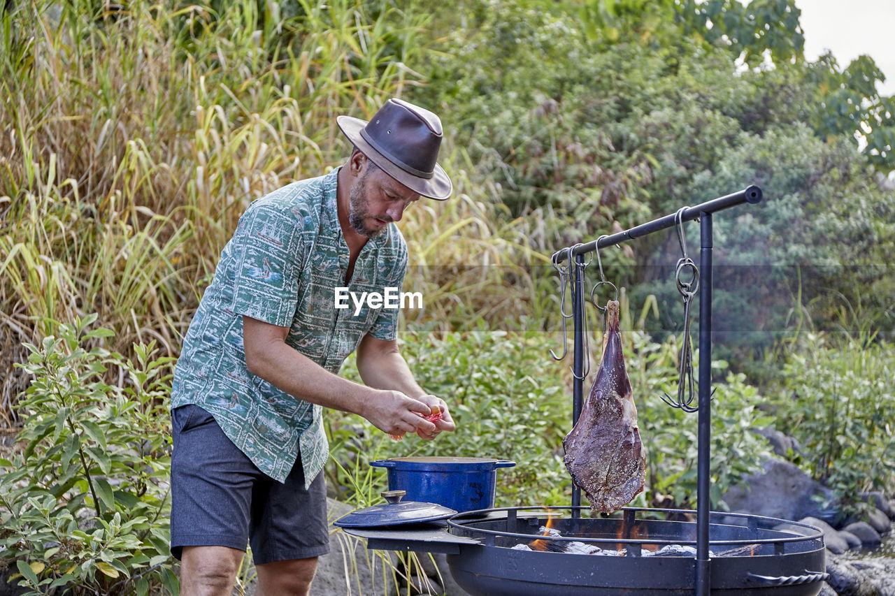 SIDE VIEW OF MAN PREPARING FOOD