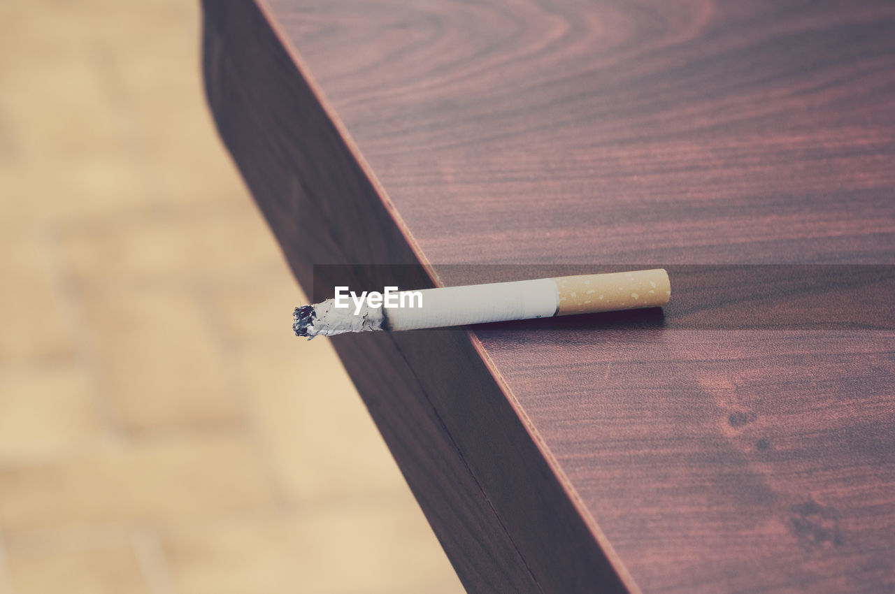 Close-up of cigarette butt on table