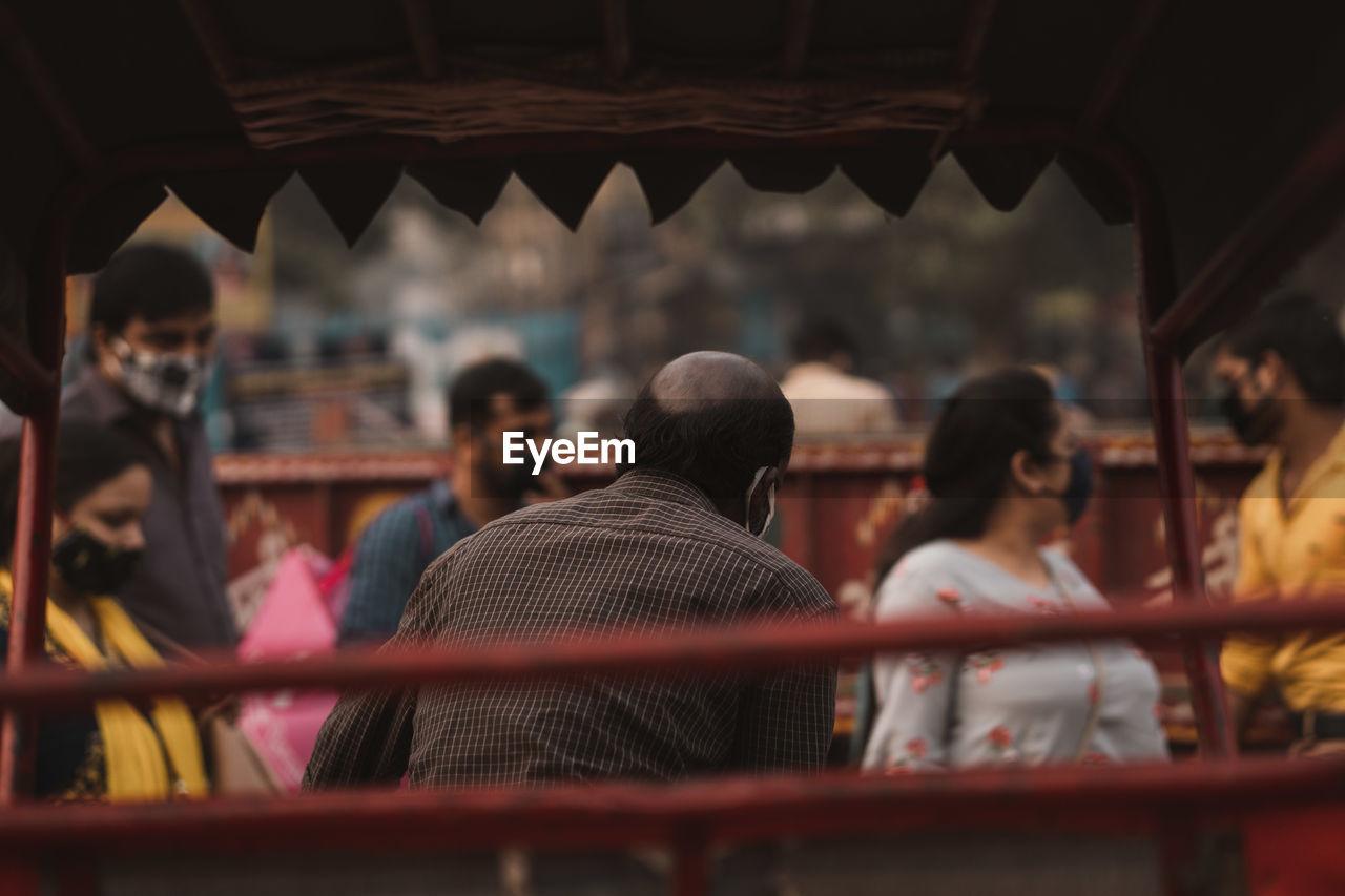 REAR VIEW OF PEOPLE AT TEMPLE SEEN THROUGH DOORWAY