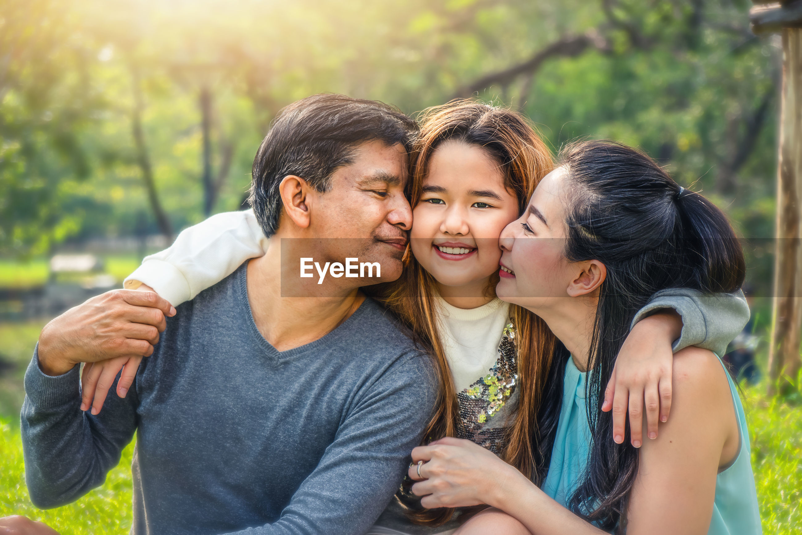Close-up of parents kissing daughter in park