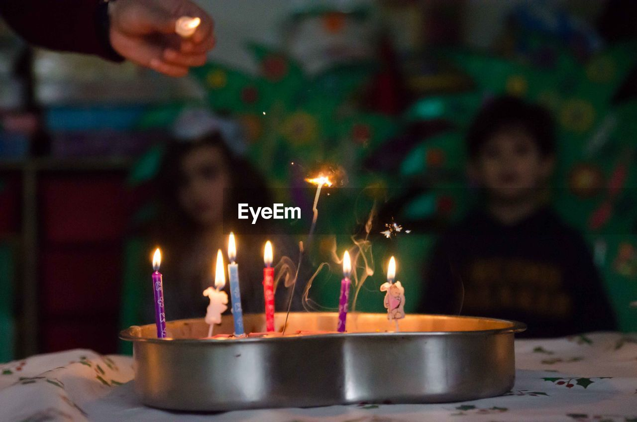 Lit candles on cake in container