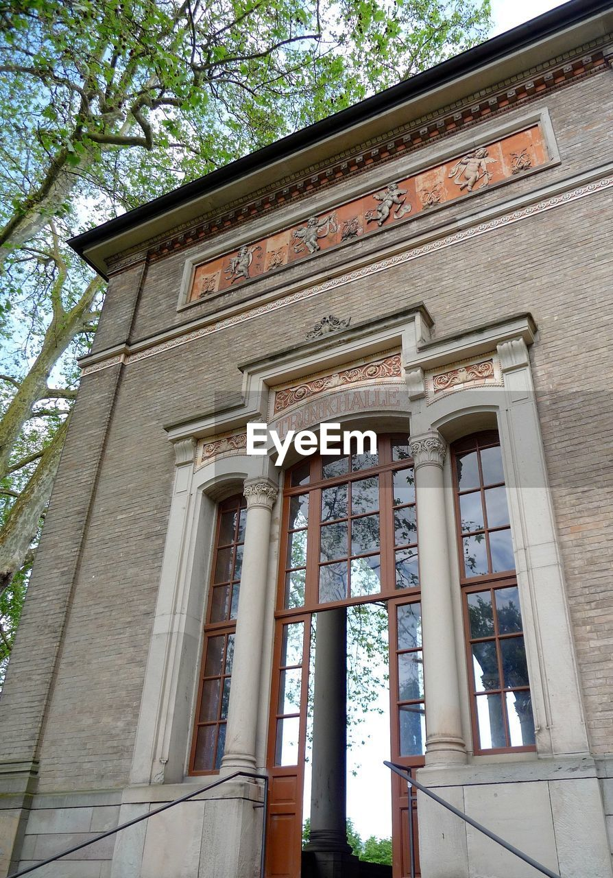 architecture, built structure, low angle view, building exterior, architectural column, day, tree, no people, window, history, wood - material, outdoors, close-up, sky, courtroom