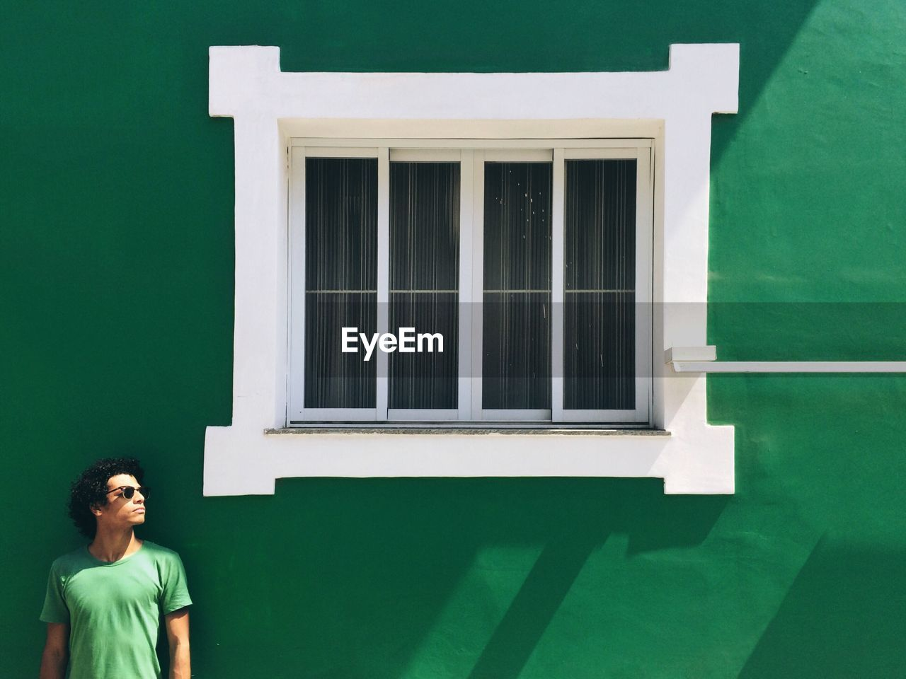 Young man looking away while standing by closed window on green wall