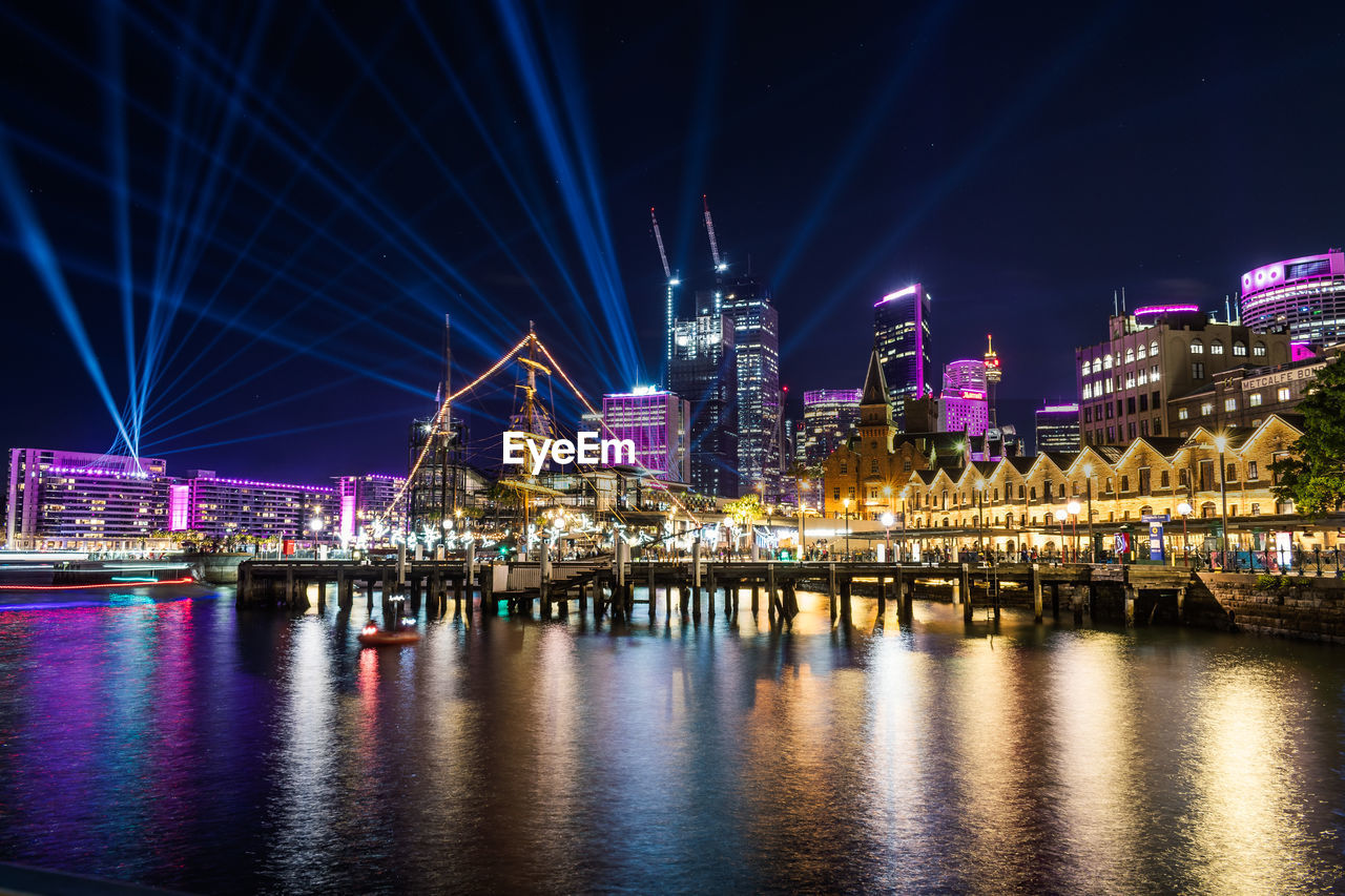 night, architecture, illuminated, built structure, building exterior, water, city, waterfront, building, river, sky, travel destinations, reflection, office building exterior, no people, cityscape, skyscraper, modern, transportation, laser, financial district, nightlife, purple