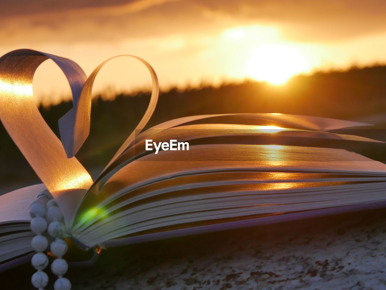 Necklace with heart shape pages of book during sunset