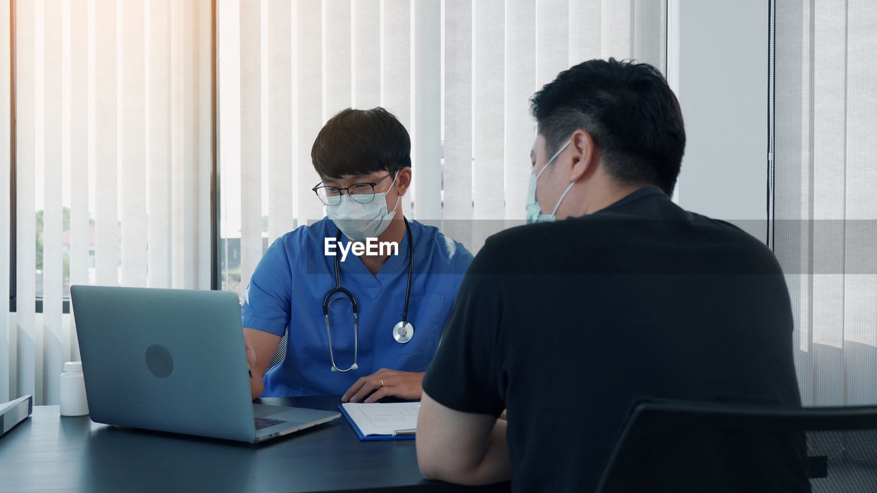 Patient and doctor wearing mask having discussion at clinic