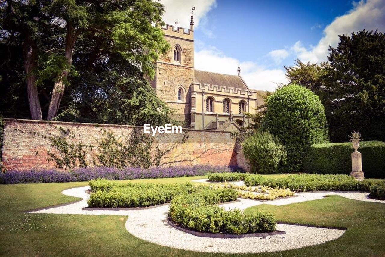 tree, plant, topiary, architecture, footpath, landscaped, green color, built structure, sky, lawn, sunlight, day, outdoors, grass, nature, building exterior, no people, flowerbed, beauty in nature