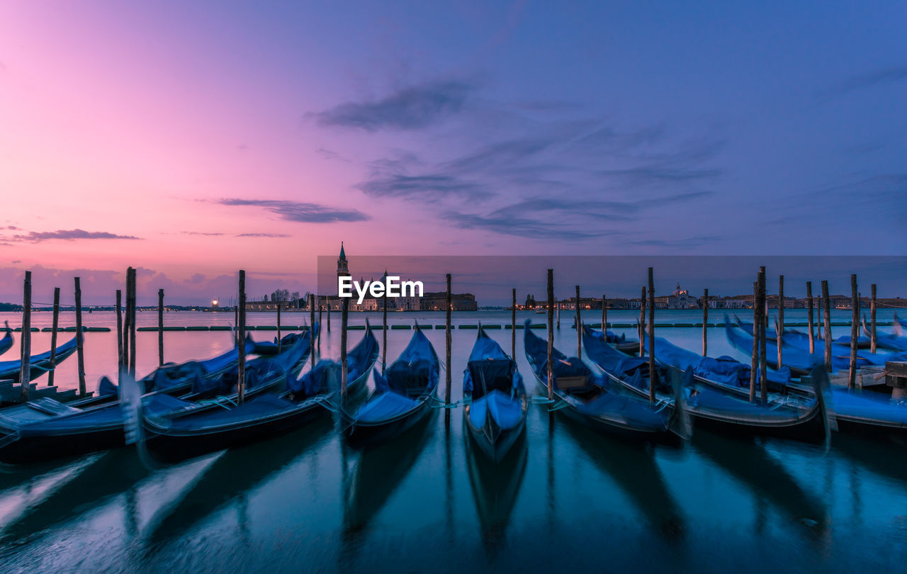 Gondolas on grand canal against sky during sunset in city