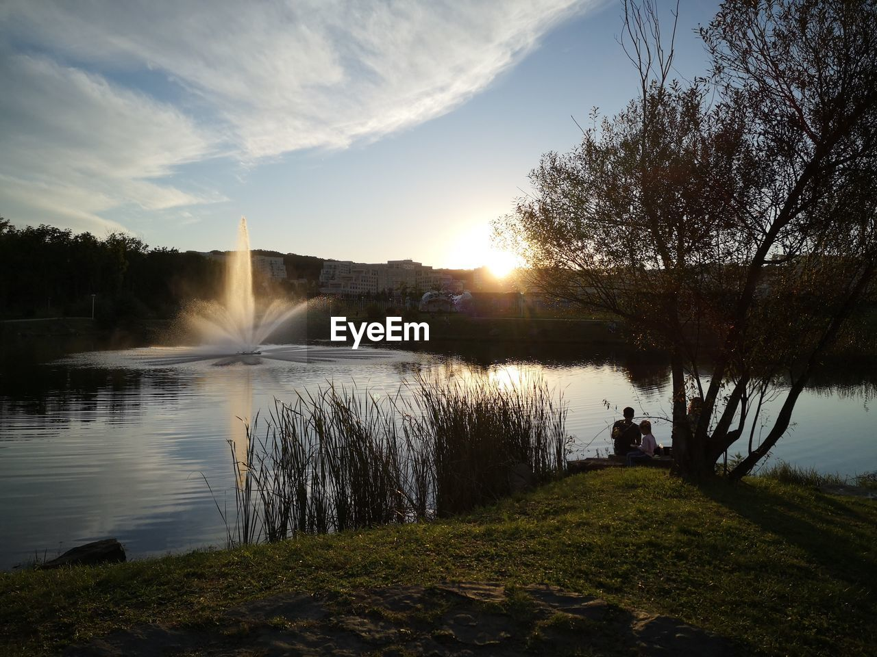water, sky, plant, scenics - nature, tree, lake, beauty in nature, nature, sun, tranquility, cloud - sky, grass, tranquil scene, non-urban scene, sunbeam, sunlight, sunset, reflection, real people, outdoors, lens flare, flowing water, spraying