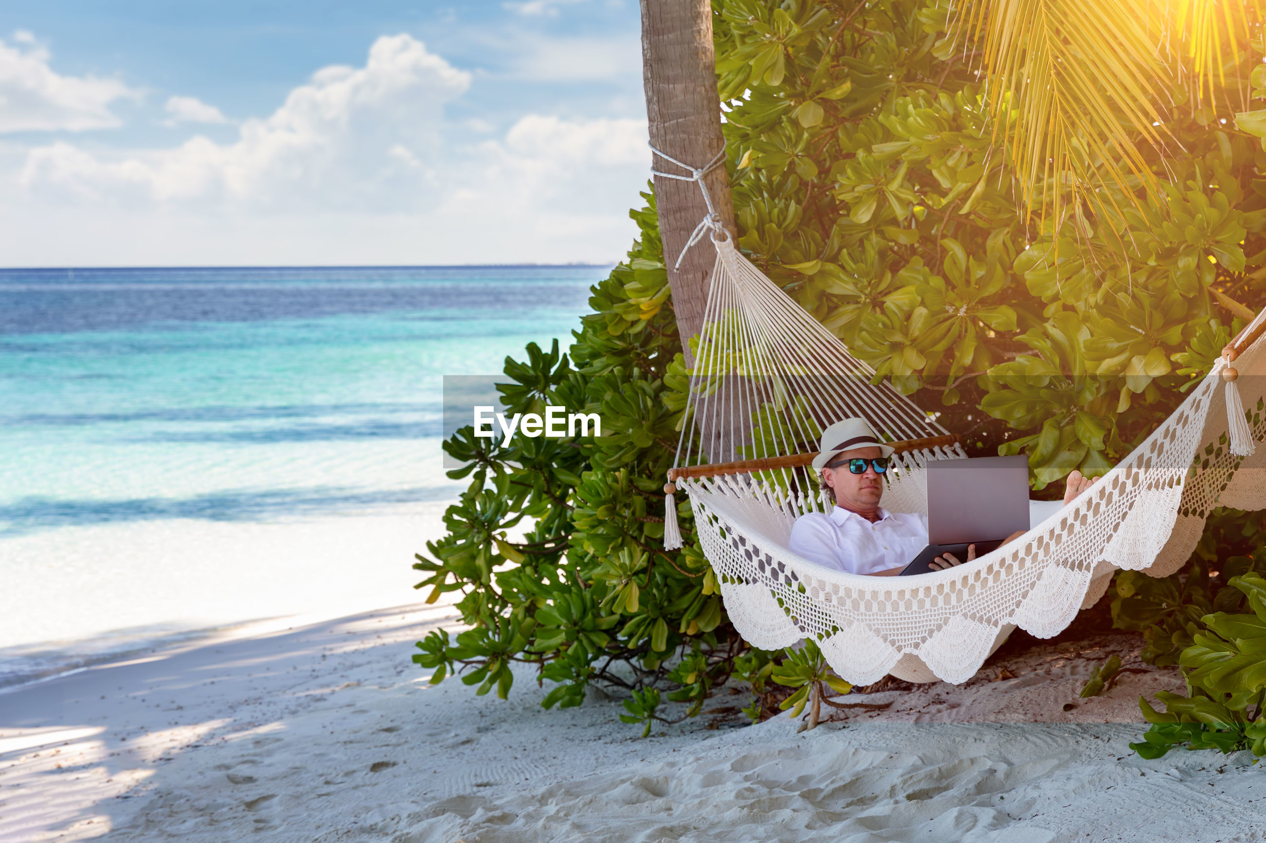 Mature man using laptop while relaxing in hammock at beach