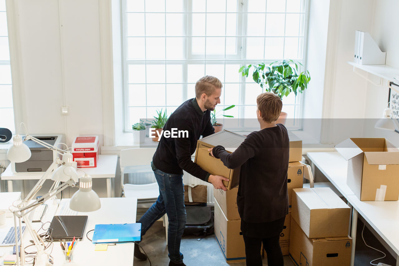 FRIENDS STANDING BY WINDOW IN OFFICE
