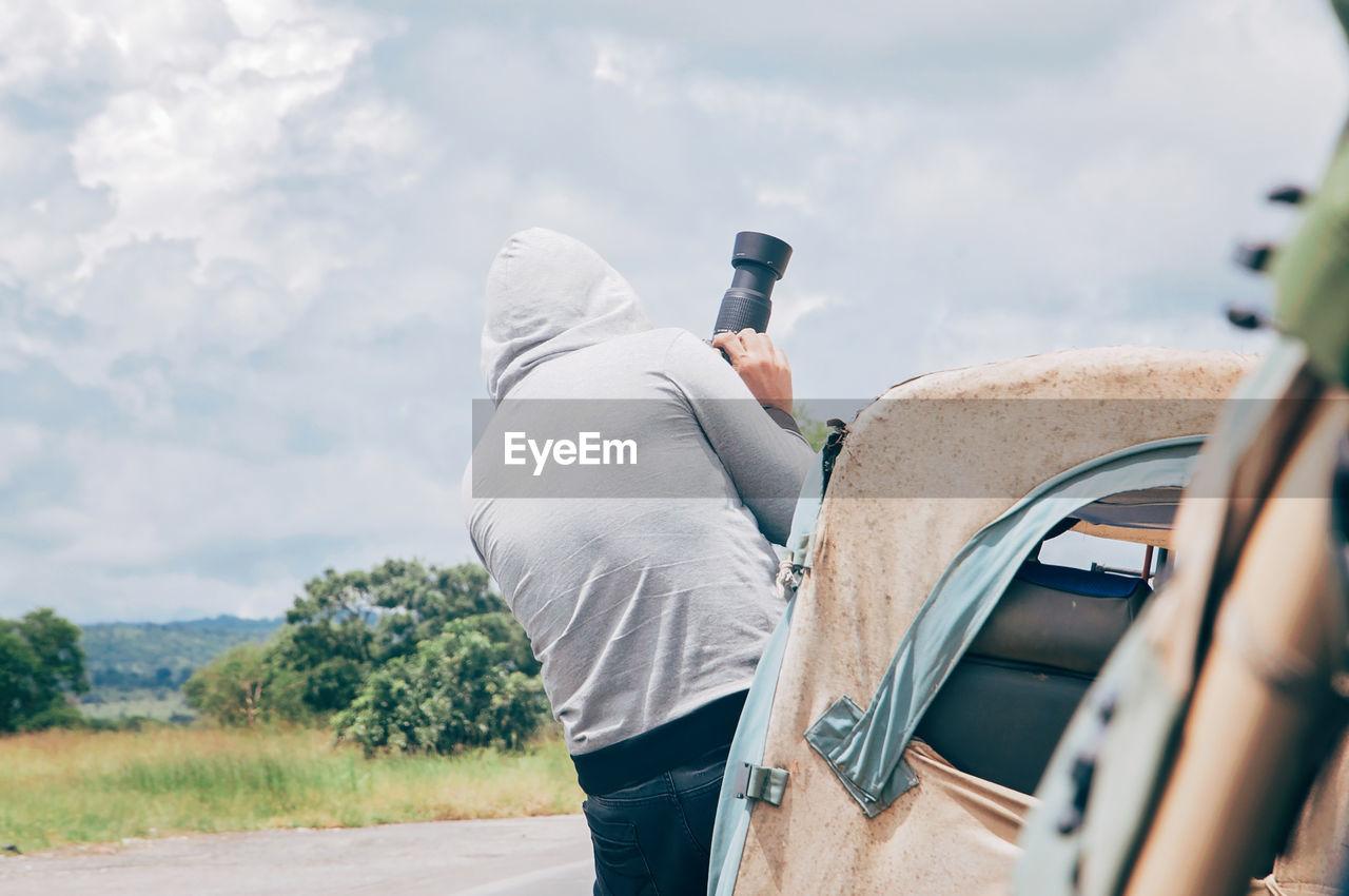 Man Using Camera Against Sky