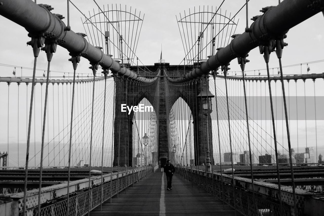 Man Walking On Brooklyn Bridge Against Sky